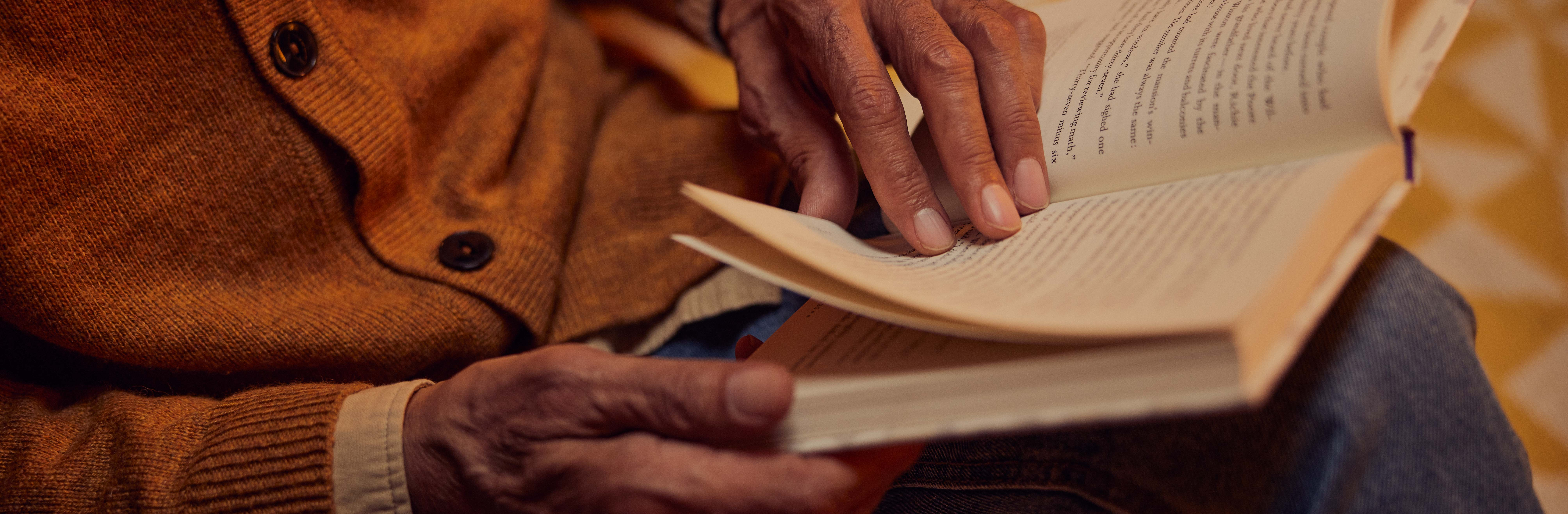 A person turning the page of a book they're reading