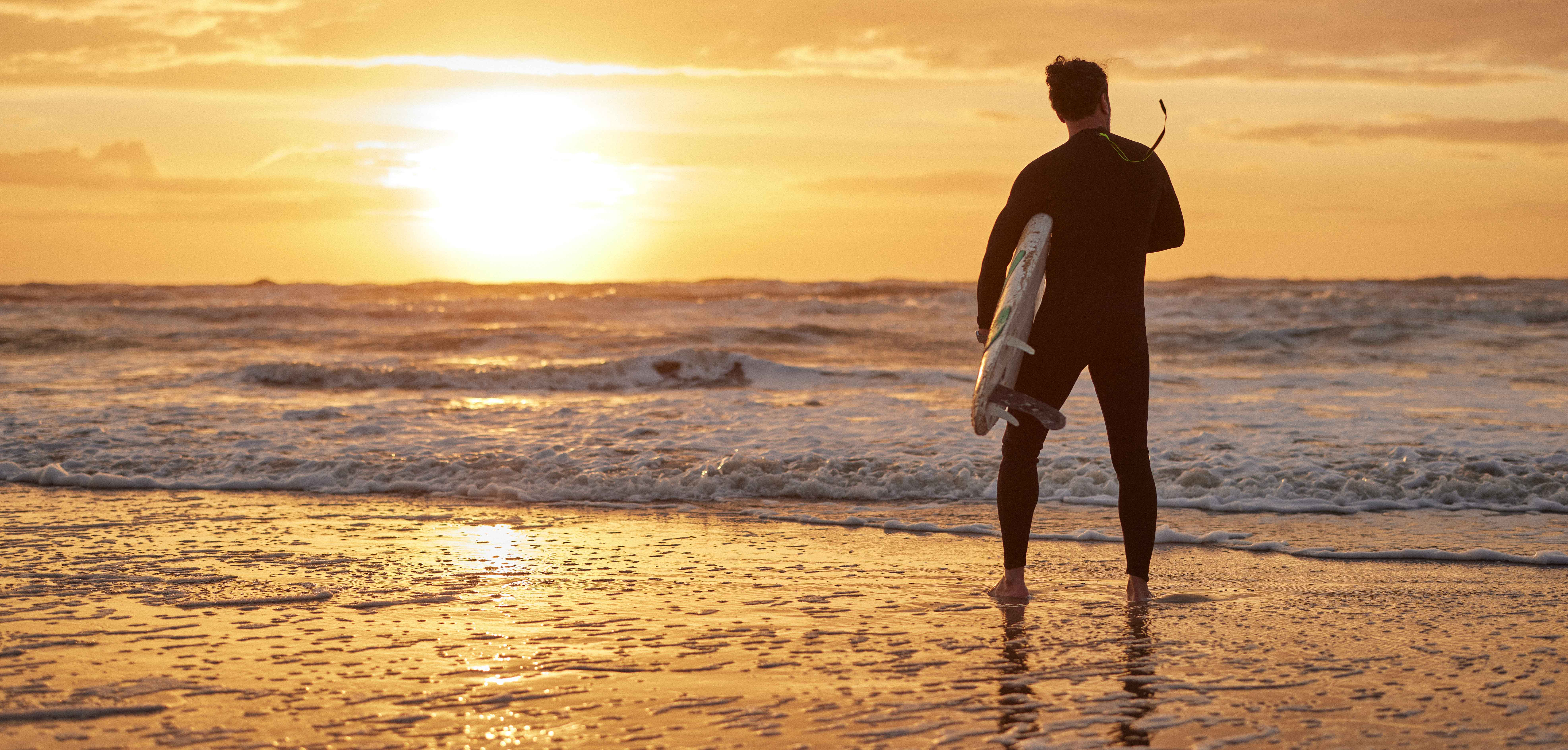 A surfer in his wetsuit analyzing the waves as the sun rises