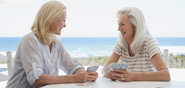 Two Women Playing Cards with an Ocean View