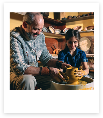 Man working on a pottery wheel with a child
